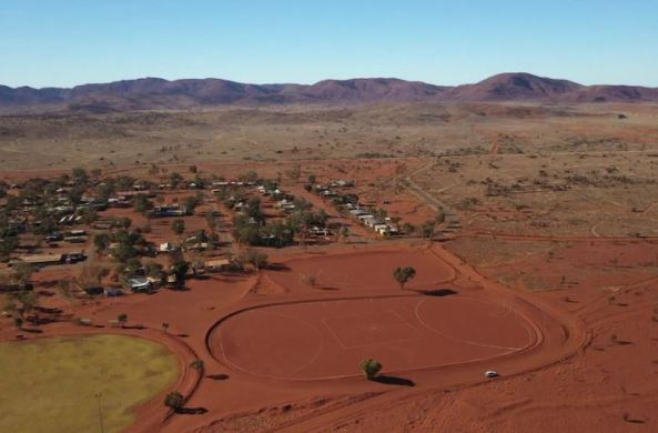 aerial view of APY Lands community Amata, red dust, approx 60 houses, dirt playing field, mountains in the distance
