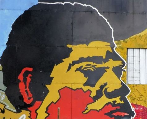 metal wall with large painting of Aboriginal man's face in black, yellow & red colours in pop art style