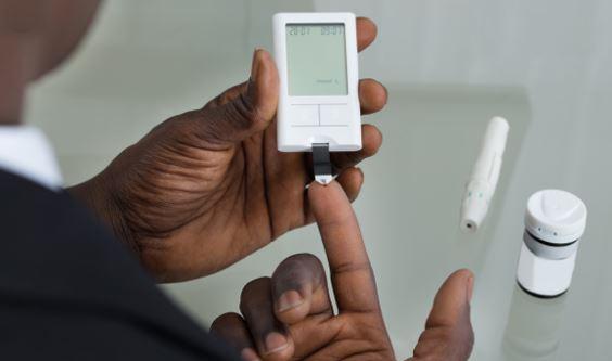 Aboriginal person's hands doing blood sugar test