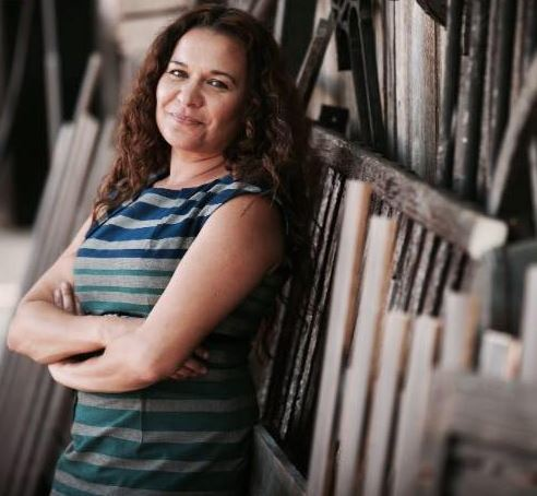 Professor Chelsea Watego, QUT, in horizontal striped dress grey navy green with arms folded leaning against wood sculpture wall