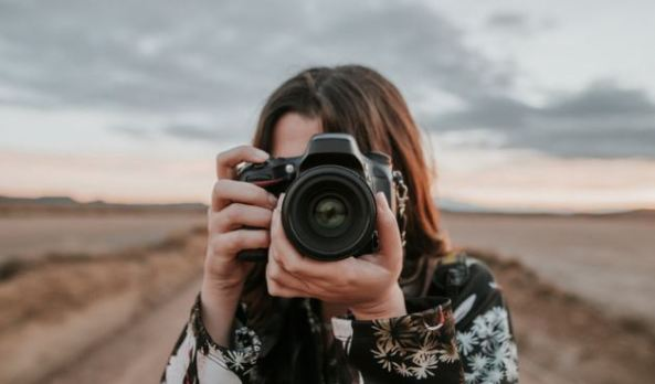 woman holding a camera to her face against dry outback blurred background