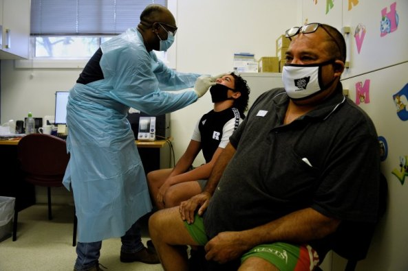 Dr Femi Olutayo (left) gives Ty Boney aged 15yrs (centre) and his father Curtis Boney from Brewarrina COVID-19 tests after they both received their first shot of a vaccination at the Ochre Medical Centre in Brewarrina. Image credit: Kate Geraghty, the Brisbane Times.