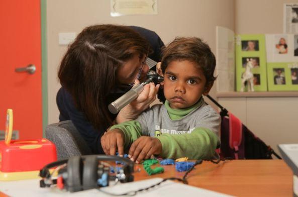 health professional checking small Aboriginal boy's ears