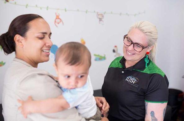 mother holding baby, IUHI healthcare worker