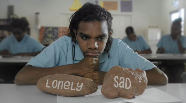 Aboriginal student resting on desk with two rocks one with the word 'lonely' & one with the word 'sad'