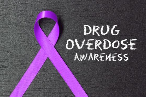 purple ribbon, black background, text in chalk font 'Drug Overdose Awareness'