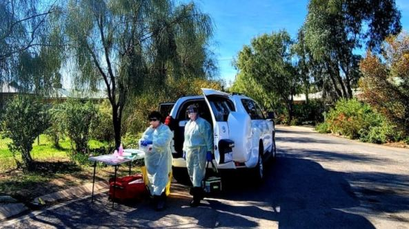 two health professionals full PPE country road back of van