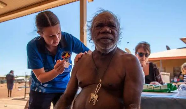elder without shirt outdoor setting receiving covid-19 vaccine from KAMS worker