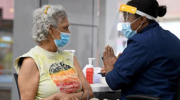 Aboriginal woman with mask & health worker with mask & face shield