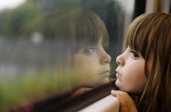 young girl gazing out a window