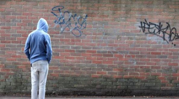 rear view of youth with blue hoodie facing brick wall with graffiti