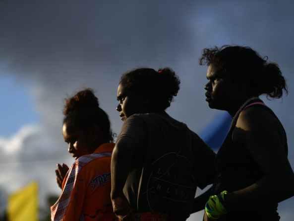 rear shot of three Aboriginal women in dim light, dusk