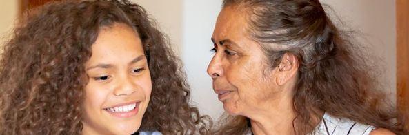 older Aboriginal woman looking in direction of smiling Aboriginal teenager (girl)