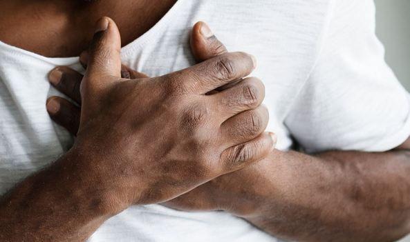 Aboriginal man's hands gripping chest - heart