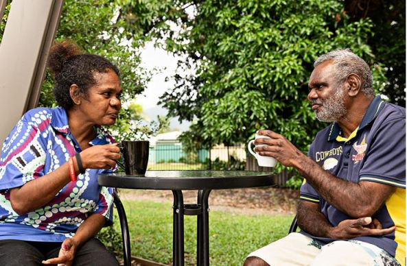 Aboriginal man and woman having a cup of tea at table