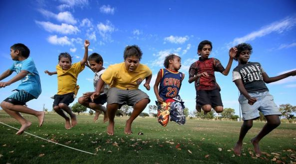 7 young Aboriginal kids jumping in the air, grass underfoot & blue sky