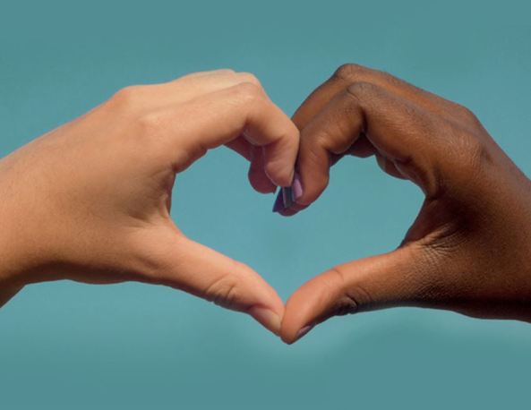 two hands of different skin colour making a heart shape