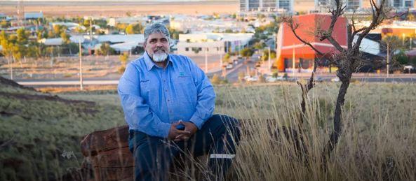 Minbaringu Director Richard Walker sitting on stump in grass field, town in background