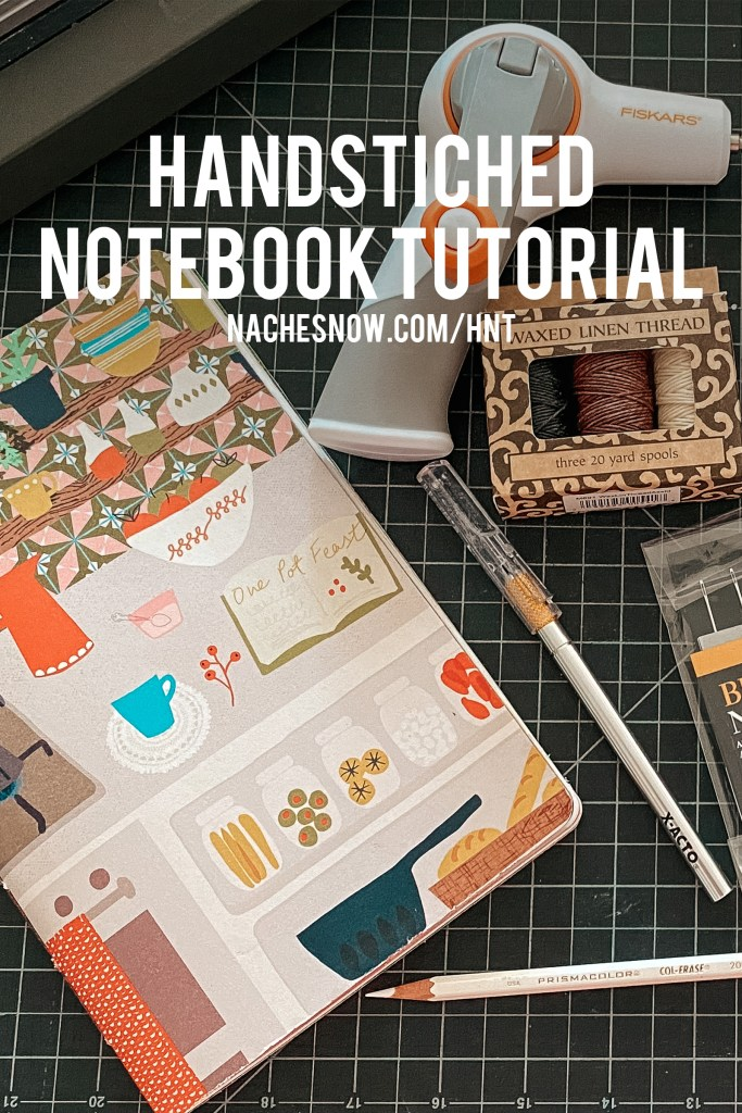 Hand-stitched notebook with illustrated cover laying on a cutting board next to a white pencil, xacto blade, waxed linen, and a Fiskars hand drill.