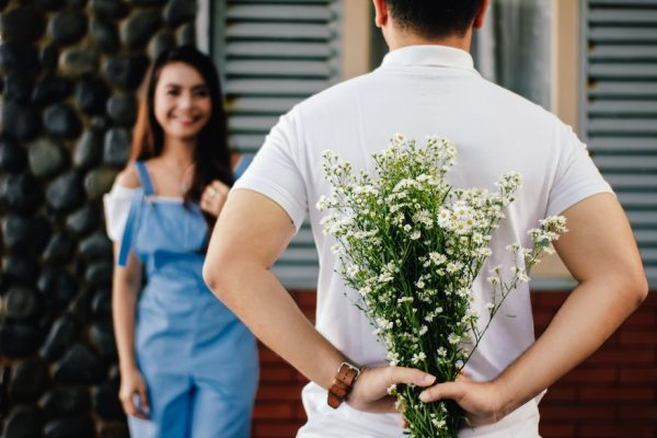 Man holding flowers behind his back as his girlfriend looks on with a smile