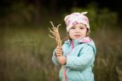 Портрет двухлетней девочке на природе среди травы.
