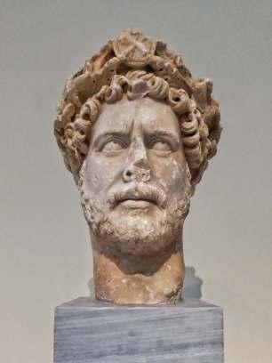 Publius Aelius Hadrianus (76 - 138) war der vierzehnte römische Kaiser. Seine besondere Wertschätzung galt der griechischen Kultur, insbesondere der als klassisches Zentrum griechischer Bildung berühmten Stadt Athen. Die Büste im Archäologischen Nationalmuseum in Athen stellt ihn mit einer Corona Civica (Bürgerkrone) dar, eine der höchsten militärischen Auszeichnungen im Römischen Reich.