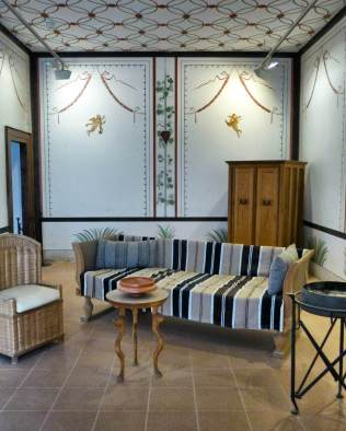 Reiseerlebnisse austauschen, Geschäfte besprechen: Rekonstruierte römische Möbel und Wandmalerei im Erdgeschoß der Herberge.