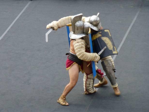 Der Murmillo im Vordergrund ist mit Kurzschwert und großem Rechteckschild bewaffnet. Er trägt am rechten Arm und am linken Bein einen Schutz. Sein schwerer Helm hat ein Visier. Er kämpft gegen den Thraex, der ein Schwert mit gekrümmter Klinge führt und mit einem kleinen Rechteckschild ausgestattet ist. Dafür trägt er an beiden Beinen Schutzschienen und am Schwertarm einen Polsterschutz. Auch er trägt einen schweren Helm mit Visier.