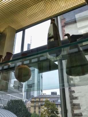 Im Seitenflügel des Neubaus blickt man durch die Ausstellungsstücke auf die Bankentürme.