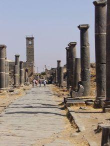 Straße mit den Säulen des römischen Nymphäums in Bosra (Syrien). Im Hintergrund der Turm einer ehemalige Moschee.