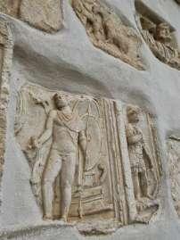 Der linke Grabstein zeigt eine Szene aus dem Troja Mythos, wie der trojanischer Fürst Äneas, Sohn der Göttin Aphrodite (Venus), aus Troja flieht und in Italien zum Stammvater der Gründer Roms wird. Rechts ist ein römischer Offizier aus severischer Zeit mit Helm, Panzer, Lanze und Militärmantel zu sehen.