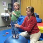 child working on balance with teacher