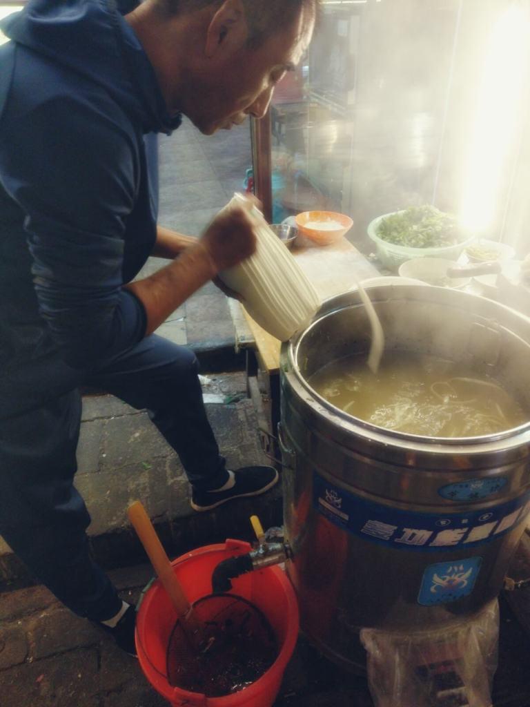 Chińczyk kroi i gotuje makaron.