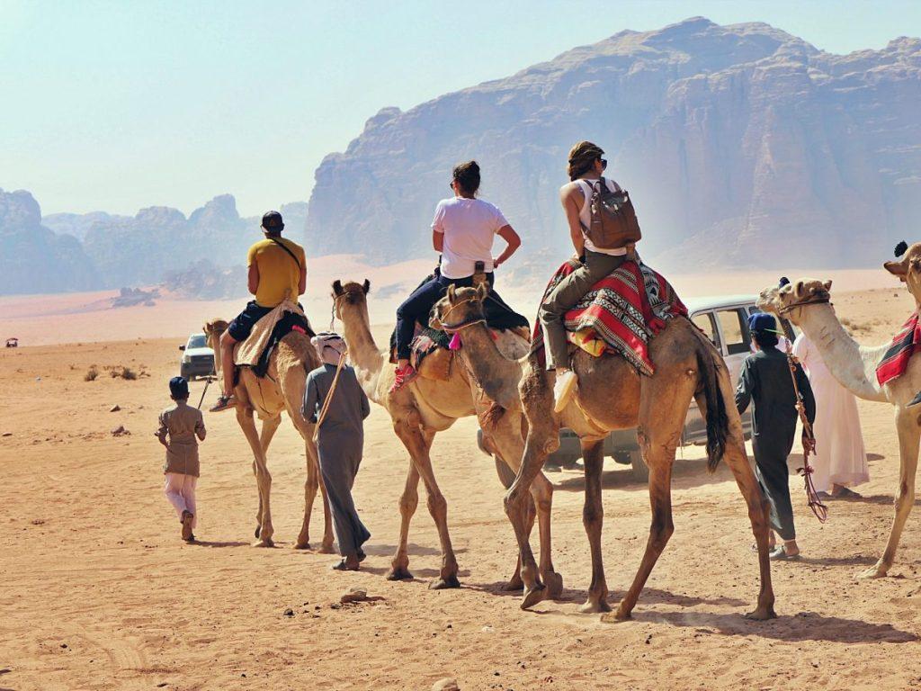 Turyści ujeżdżają wielbłądy na pustyni Wadi Rum.