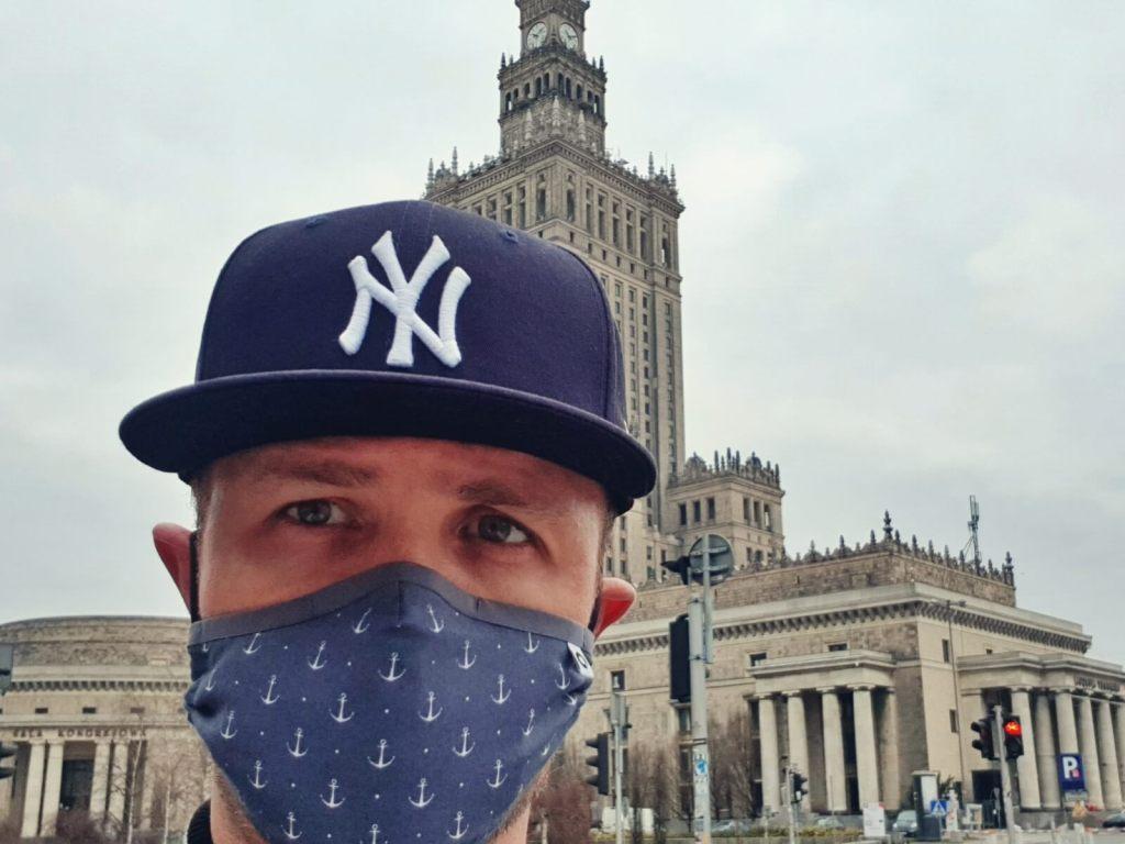 Bloger podróżniczy w masce na tle Pałacu Nauki i Kultury w Warszawie.