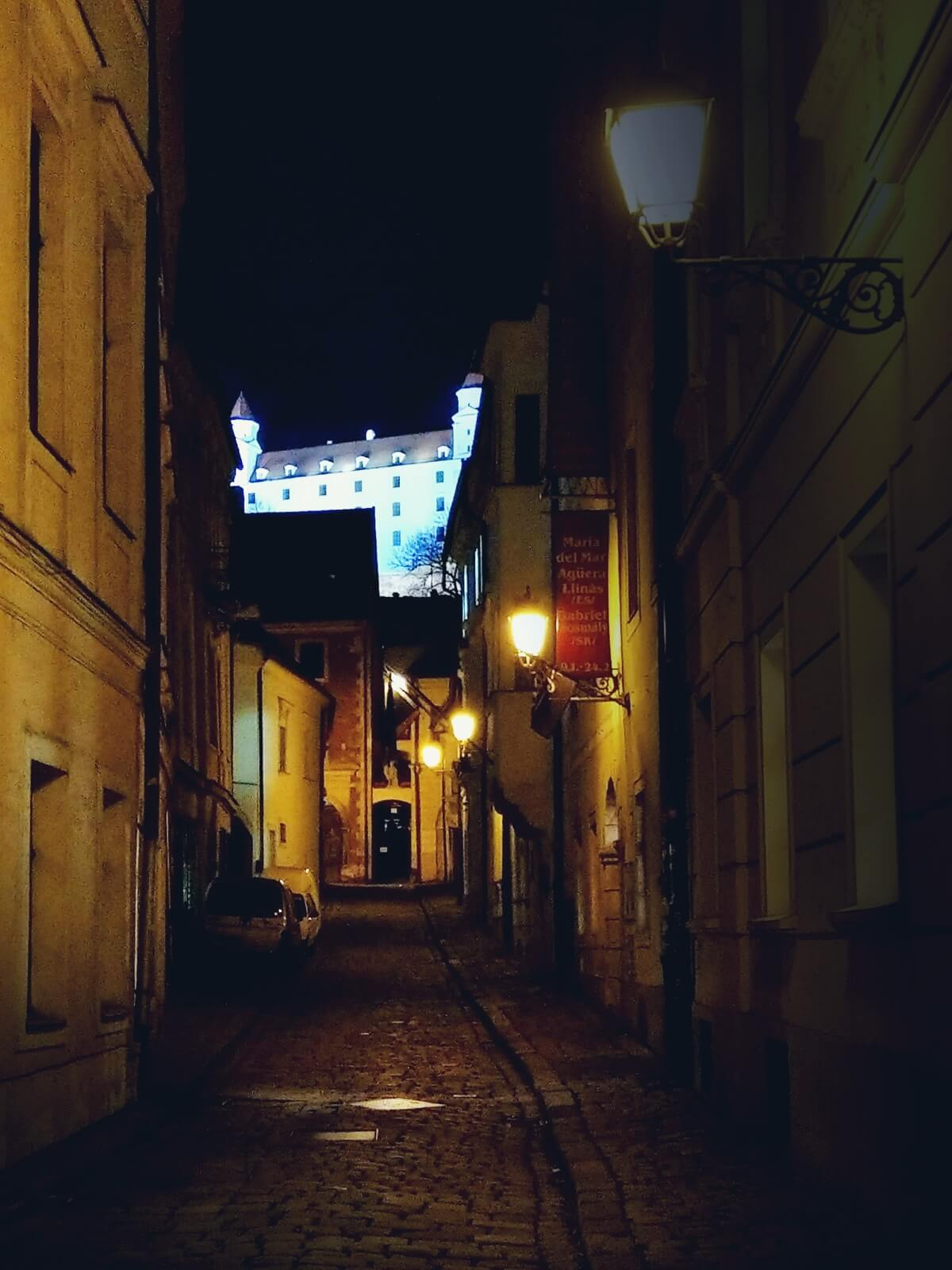 Uliczki starego miasta i biały zamek w Bratysławie nocą.
