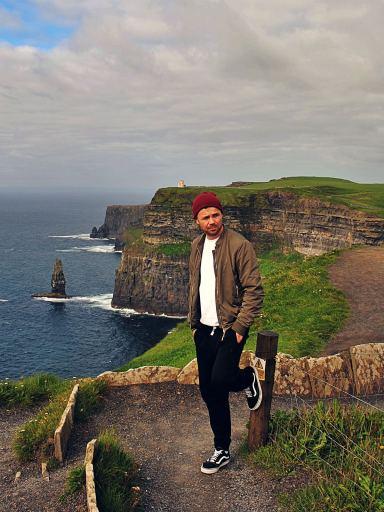 Bloger podróżniczy pozuje na tle klifów Moheru w Irlandii.