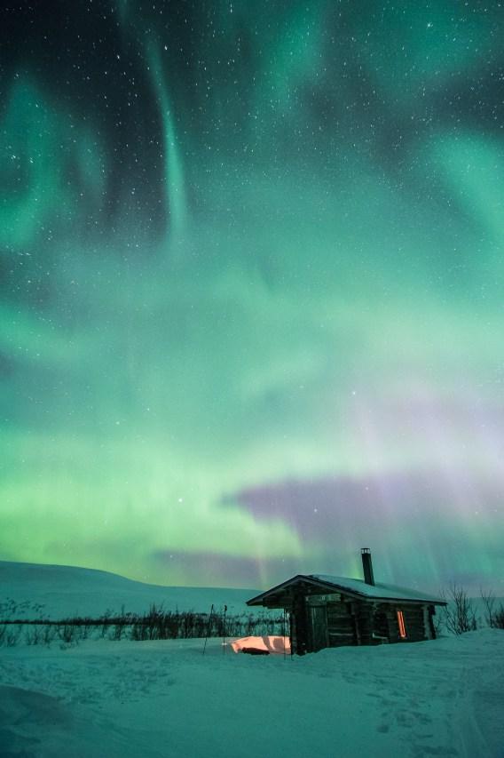 Die Ropihütte unter Polarlichtern