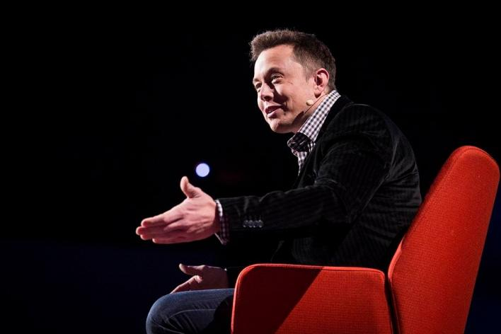 Elon Musk sitting on a red chair and speaking - widly successful modern africans