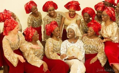 photo: bride's friends wearing red and gold aso-ebi colours