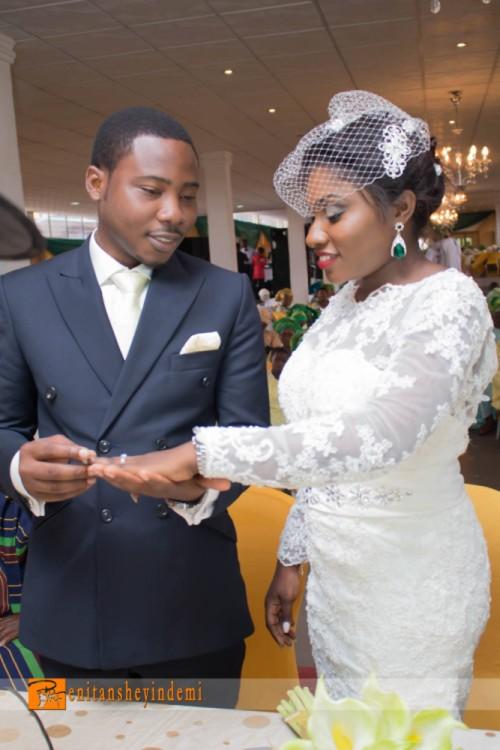 nigerian groom slipping ring into bride's finger