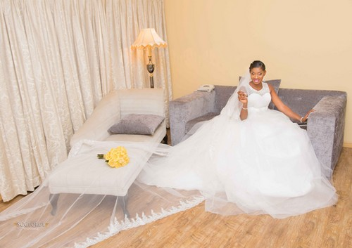 bride poses in short-sleeved wedding gown snd yellow bouquet