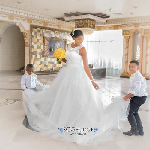 Bride poses with ring bearer boys