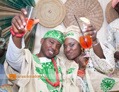 yoruba couple in green aso-oke toasting to a drink