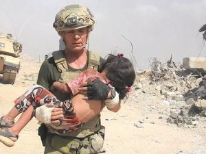 Dave Eubank carrying a little girl to safety with help of US military & Iraqi Army