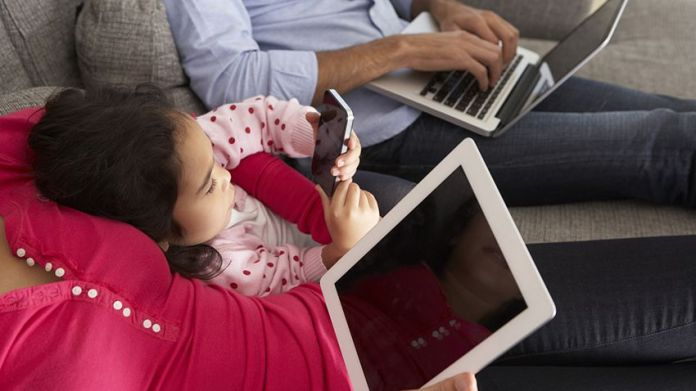 Family On Sofa Using Smartphone, Laptop And Digital Tablet