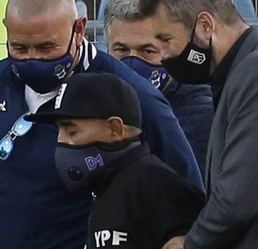 Diego Maradona wearing a DM face mask and flanked by two men