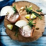 looking down on two apple cider moscow mules on a wooden serving platter