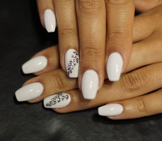 Uñas acrílicas blancas decoradas con piedras