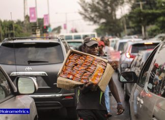 A young man hawks biscuit in Lagos traffic